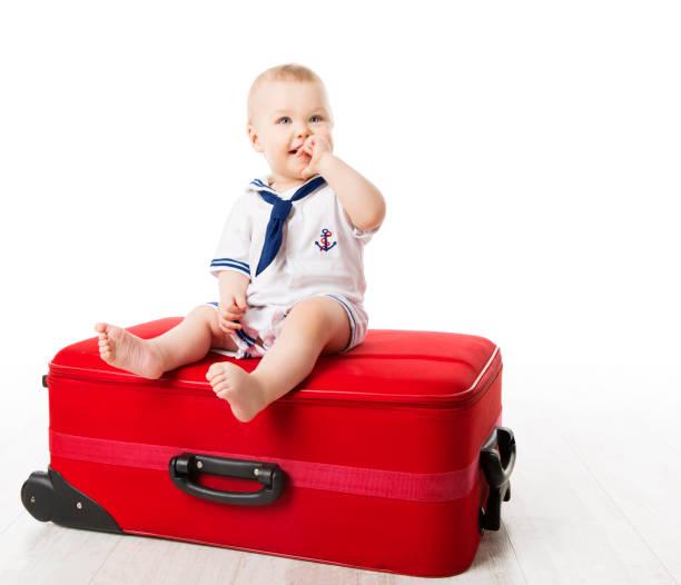 kind auf reisen, baby boy sitzt auf rotem gepäck, ein jahr altes kind - kleinkind busy bags stock-fotos und bilder