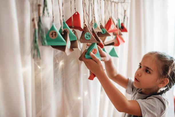 kind öffnen handgemachte adventskalender mit farbe papier dreiecke. saisonale aktivität für kinder - adventskalender stock-fotos und bilder