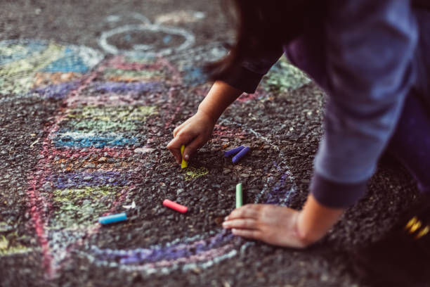 kid painting on the ground - chalk drawing stock photos and pictures