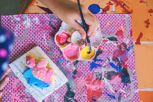 kid painting on the plaster statue. - handbemalte teller stock-fotos und bilder