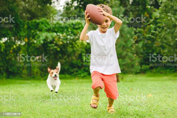 Kid playing american football ready to make touchdown and dog chasing picture id1138228616?b=1&k=6&m=1138228616&s=612x612&h=lxayujixzd7yd42xl6ol78gmvva8opbeizxskt2xrsy=