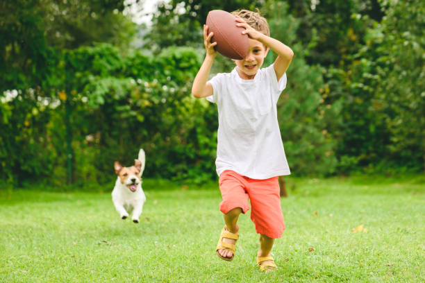 Kid playing american football ready to make touchdown and dog chasing picture id1138228616?b=1&k=6&m=1138228616&s=612x612&w=0&h=cpct e5kg0n5rkqpxs56 wgydmysjgd7h 50h mc8pe=