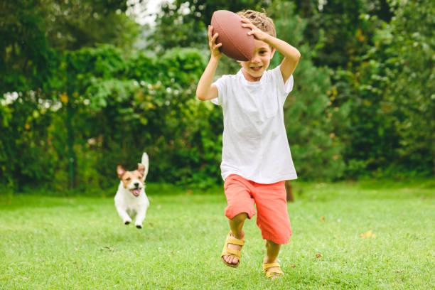 Kid spelen American Football klaar om touchdown en hond jagen hem te maken foto