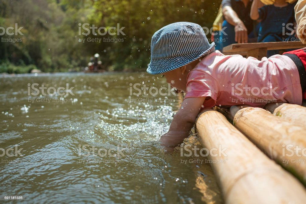 Kid playing at the edge of bamboo raft stock photo