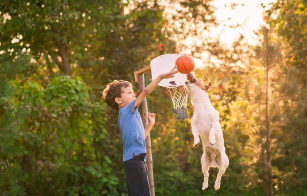 Kid Playing basketbal met zijn hond in achtertuin tuin foto