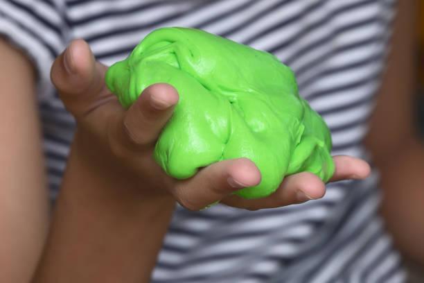 Niño jugando juguete hecho a mano llamado limo, método científico experimento - foto de stock
