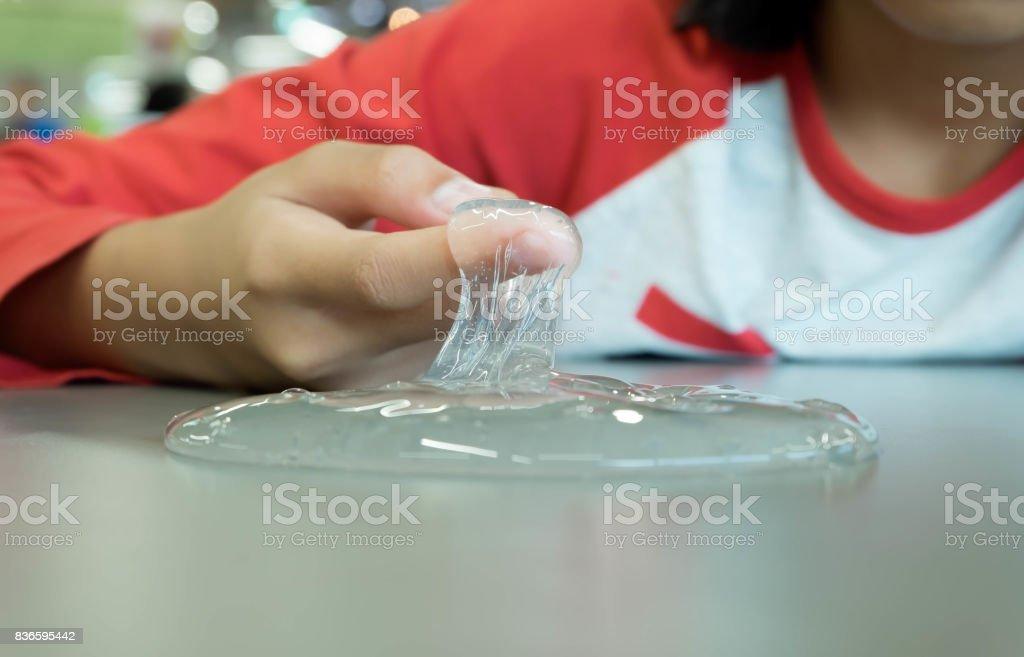 Niño jugando mano hecha juguete llamado Baba, selectivo se centran en limo, adolescente divertirse y ser creativo Baba casera. - foto de stock