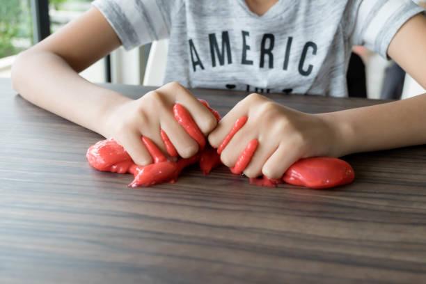 Niño jugando a mano juguete llamado Baba, selectivo foco en limo, adolescente divertirse y ser creativo Baba casera - foto de stock