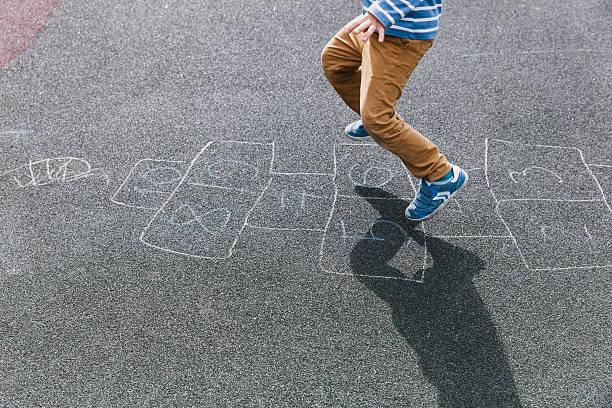 kid playing hopscotch on playground, kids outdoor activities - himmel und hölle spiel stock-fotos und bilder