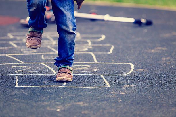 kinder spielen am spielplatz im freien himmel-und-hölle-spiel - himmel und hölle spiel stock-fotos und bilder