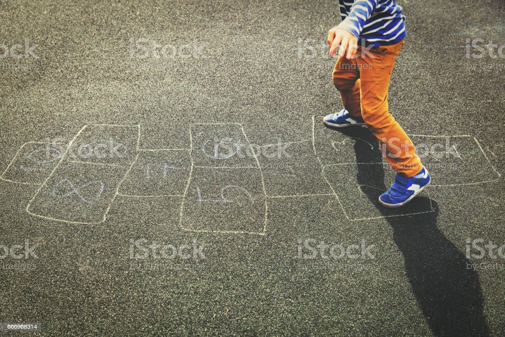 kid playing hopscotch on playground stock photo
