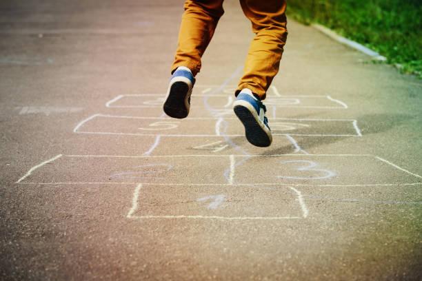 kind spielt auf spielplatz himmel-und-hölle-spiel - himmel und hölle spiel stock-fotos und bilder