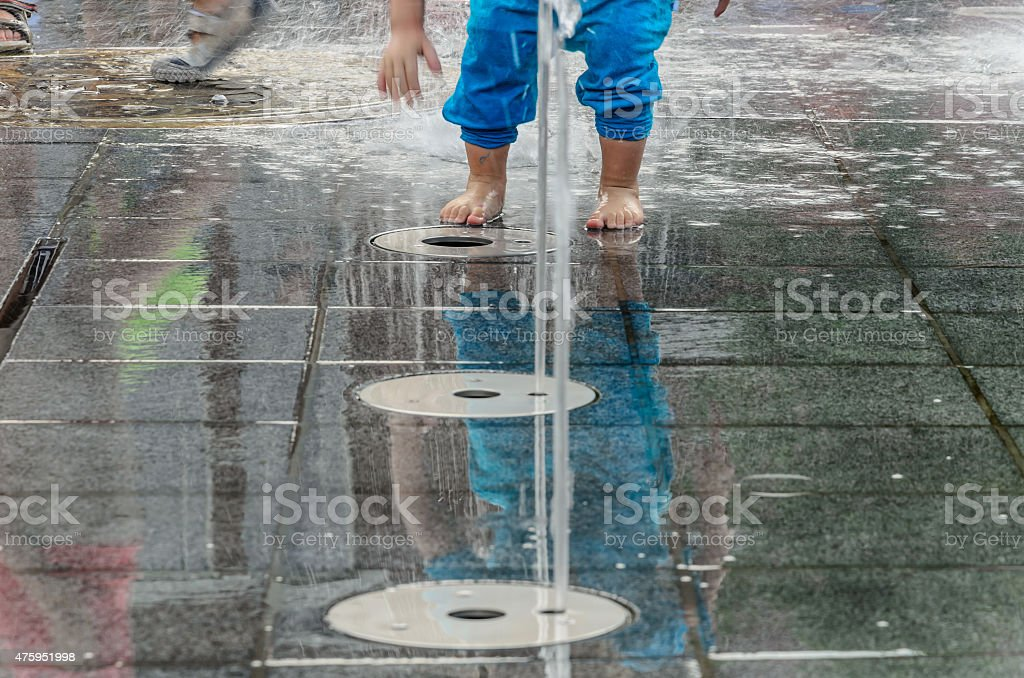 Kid playing in fountain stock photo