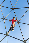 Kid out in playground climbing on spider web.