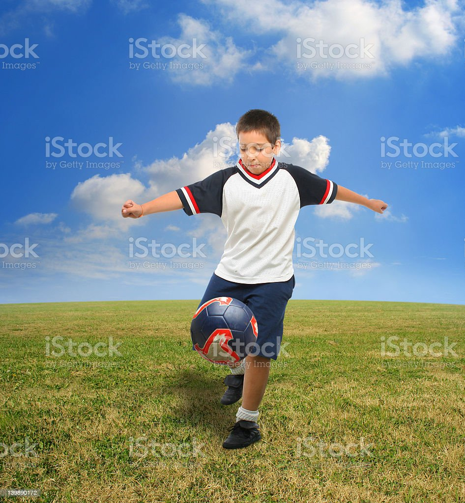 Kid playing soccer outside royalty-free stock photo