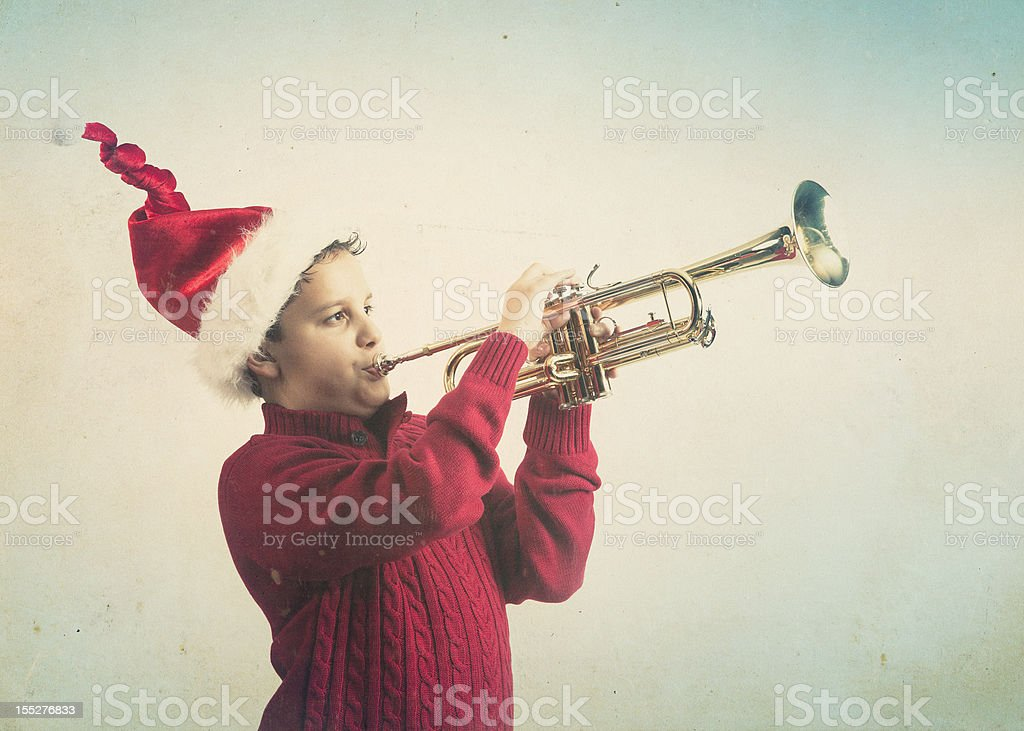 kid playing the trumpet wearing santa hat stock photo