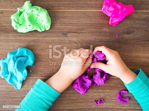 istock Kid playing with a modeling compound on a dark background 846232866