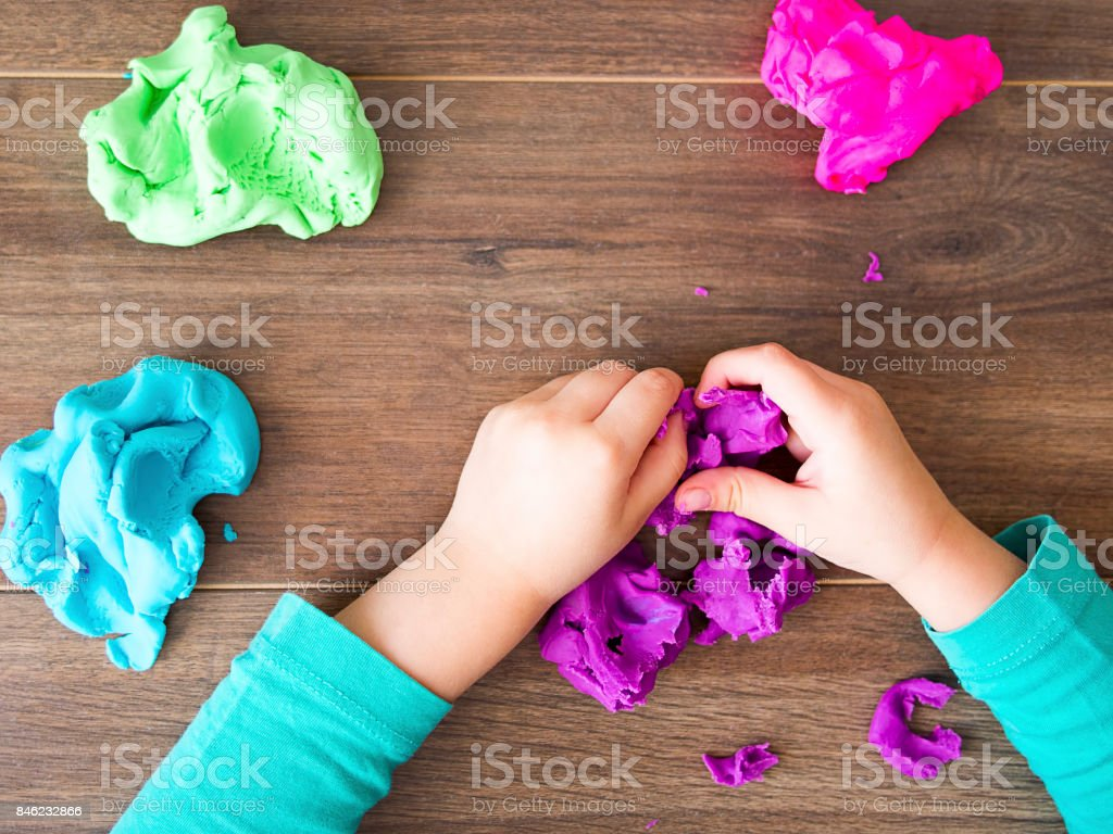 Kid playing with a modeling compound on a dark background stock photo