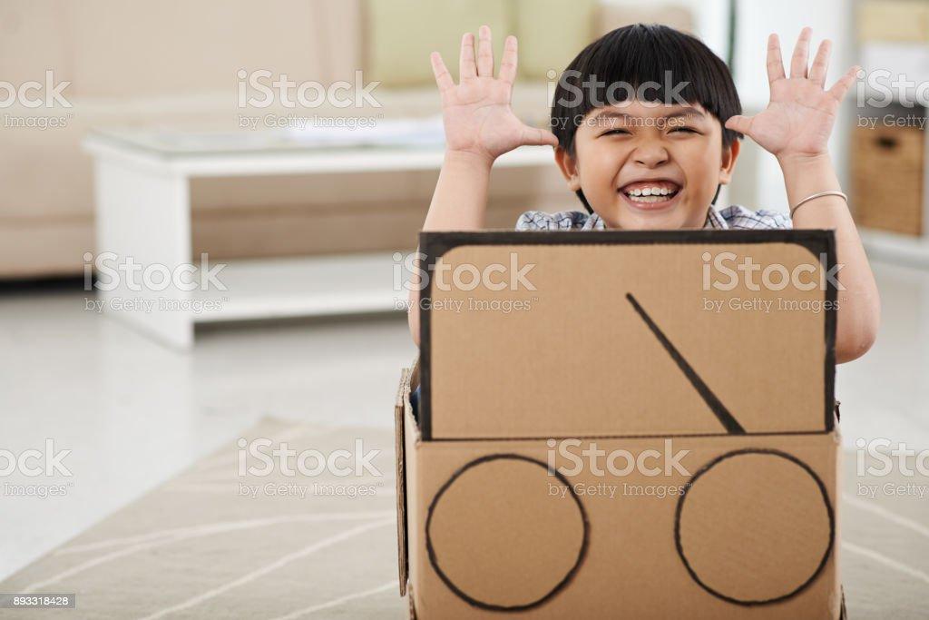 Kind spielt mit Pappe Auto – Foto