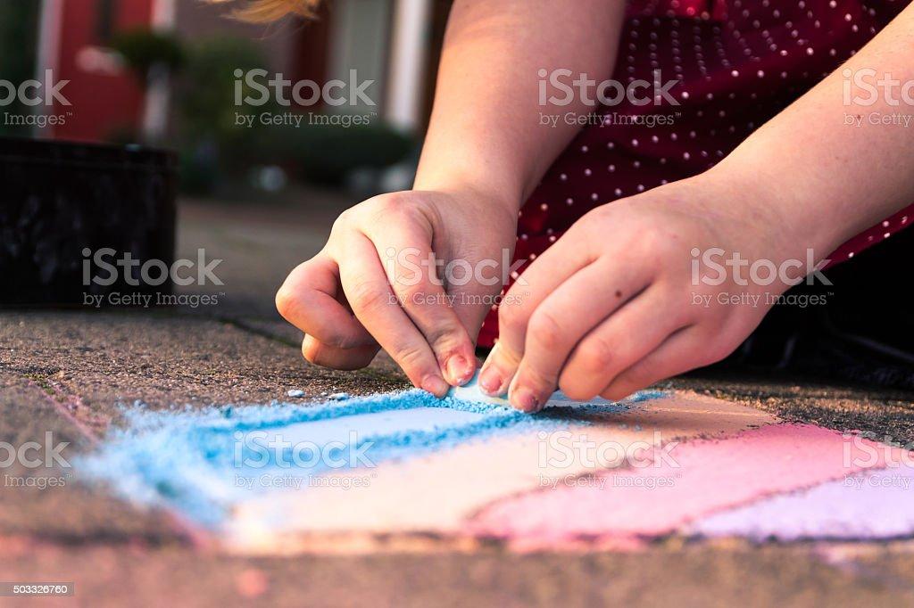 Kind spielt mit farbigen Kreide auf dem Bürgersteig stehen. – Foto