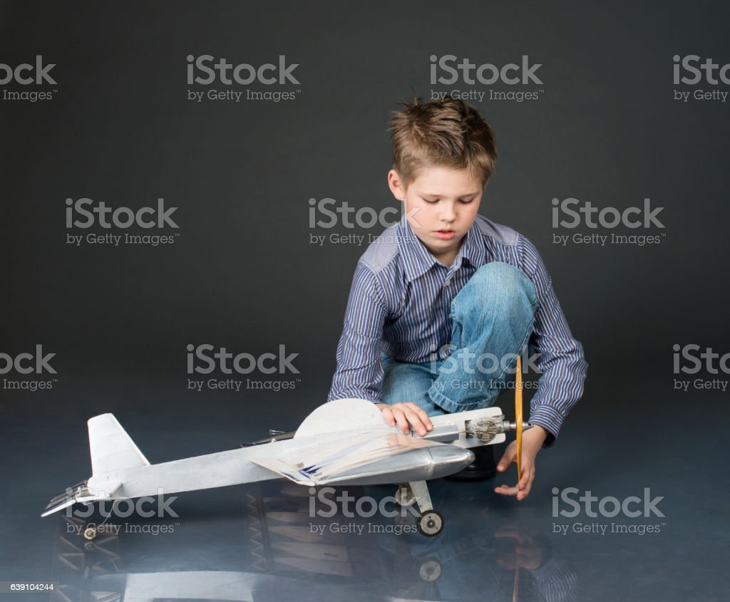 Kid playing with handmade plane glider. Boy holding wooden plane stock photo