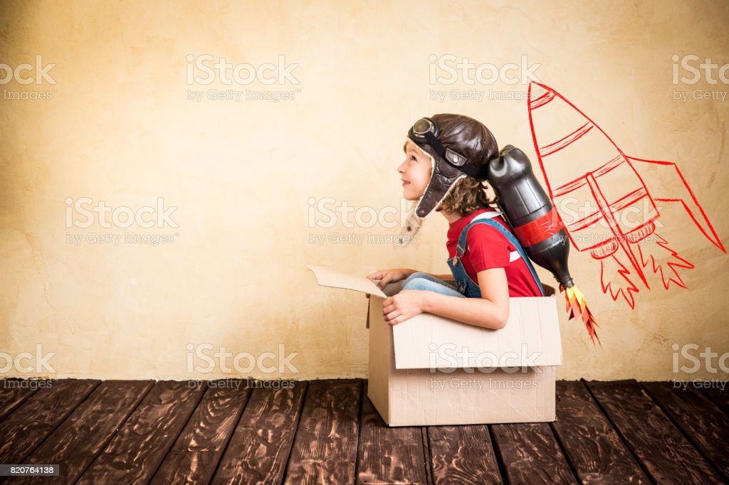 Kid playing with jet pack at home stock photo