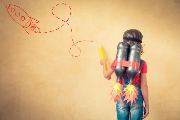 Criança brincando com uma mochila a jato em casa - foto de acervo
