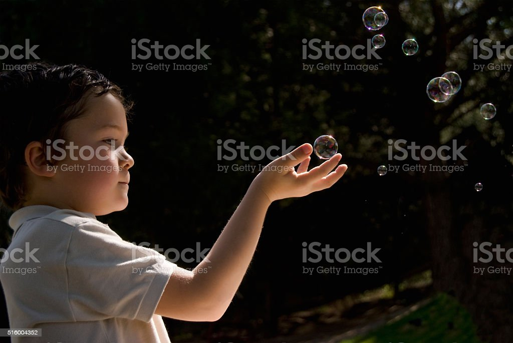 Kid playing with soap bubbles. stock photo