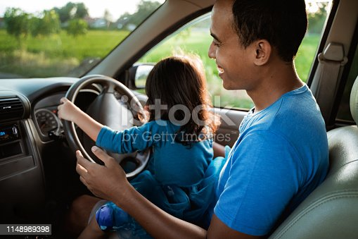 972962180 istock photo kid playing with steering wheel dad 1148989398
