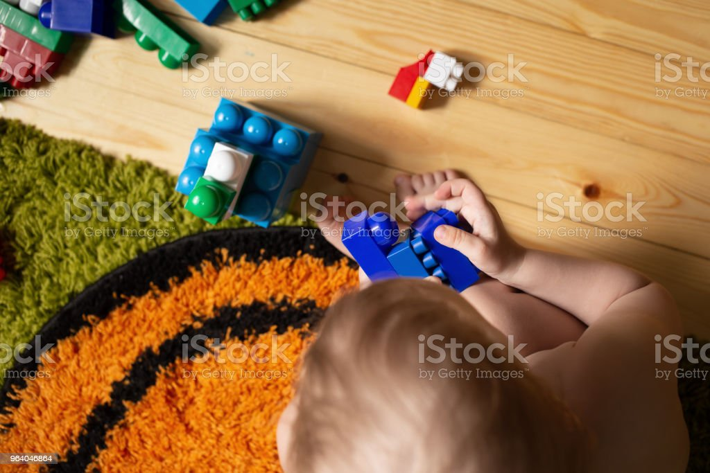 kid playing with toy blocks on the carpet - Royalty-free Above Stock Photo