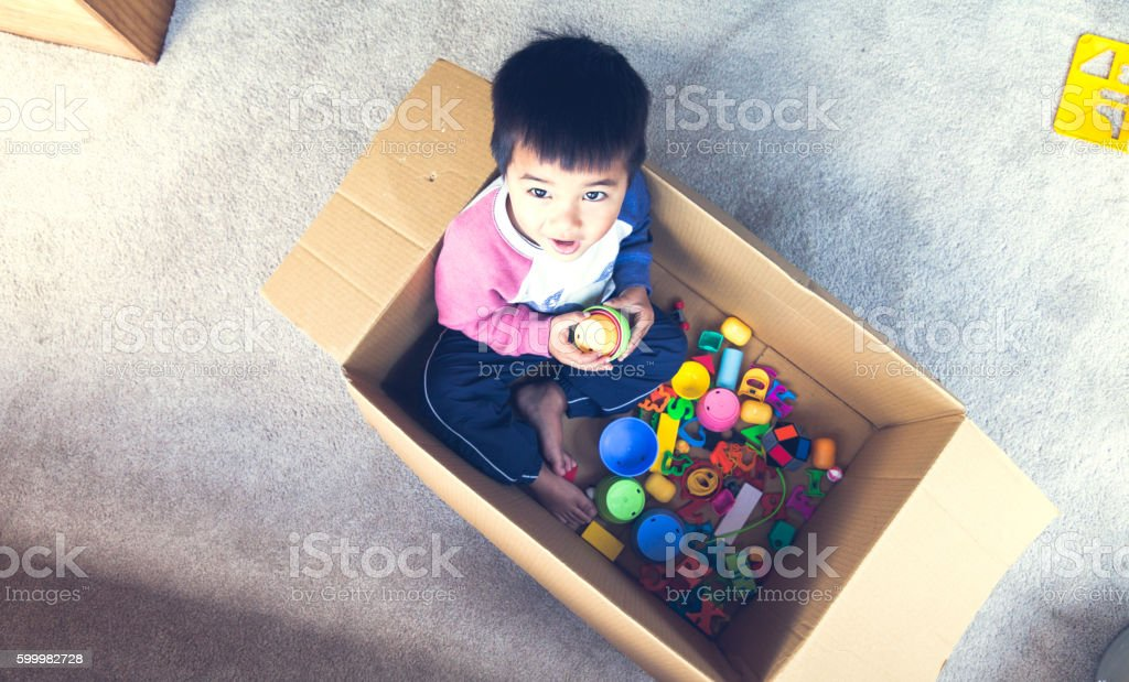 Kid in a cardboard box playing with toys and looking upwards.