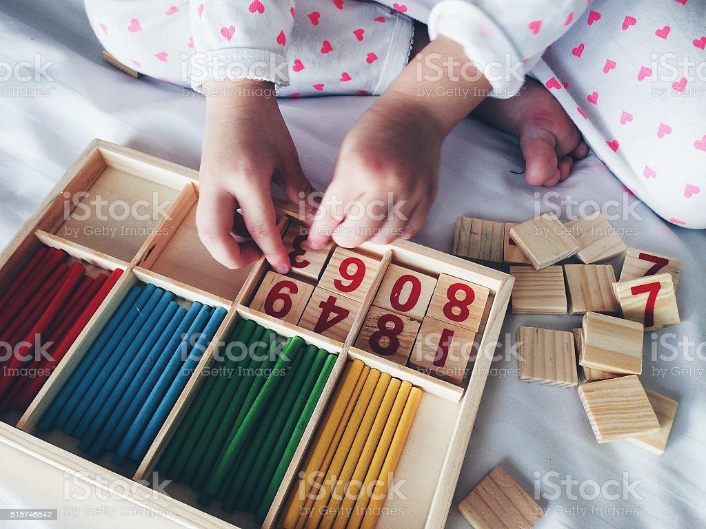 Kid playing with wooden numbers and color sticks stock photo