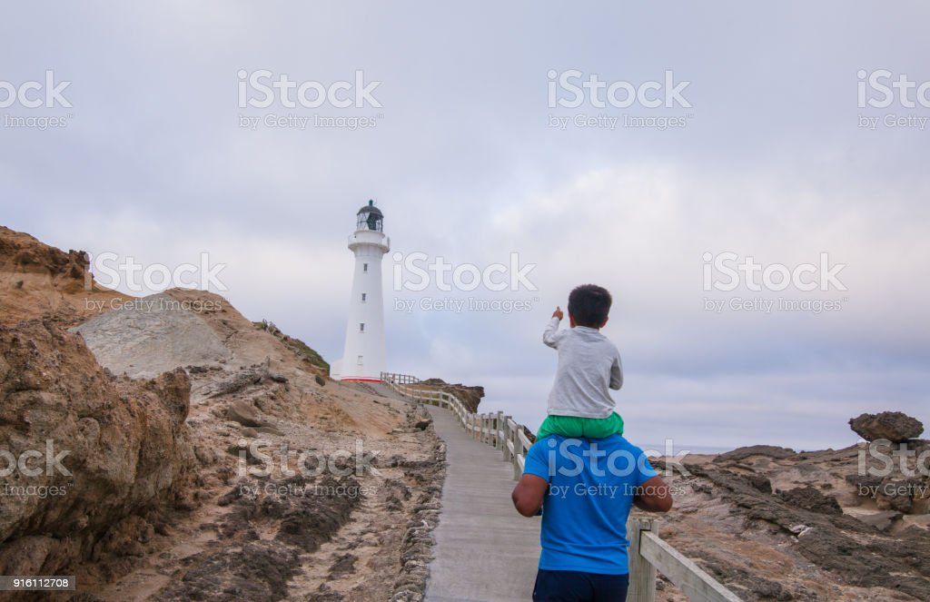 Kid pointing at Castlepoint Lighthouse while riding on father shoulders. stock photo