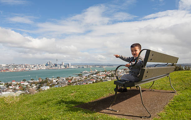 Kid pointing towards Auckland City. Kid sitting on a bench at Mt Victoria and pointing towards Auckland city over Devonport. mt victoria canadian rockies stock pictures, royalty-free photos & images