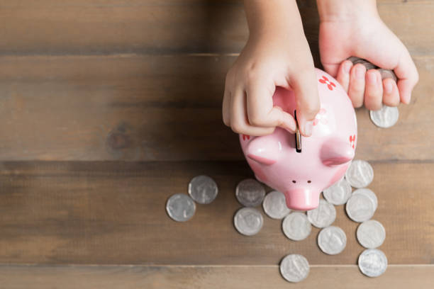 kid put coin to piggy bank on the vintage wood background stock photo