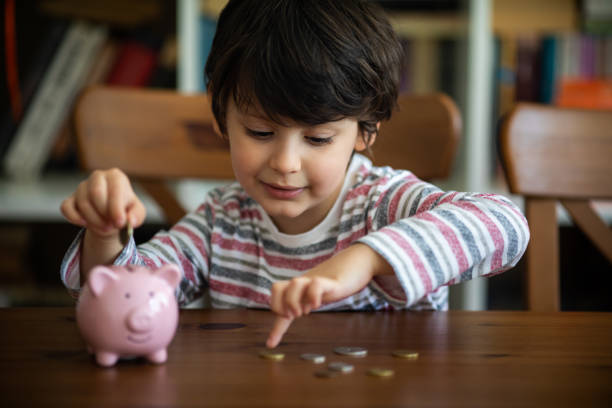 Kid put coin to piggy bank stock photo