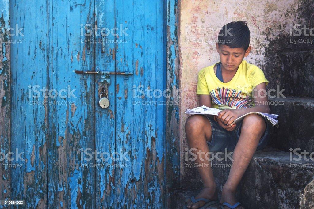 kid reading near locked door stock photo