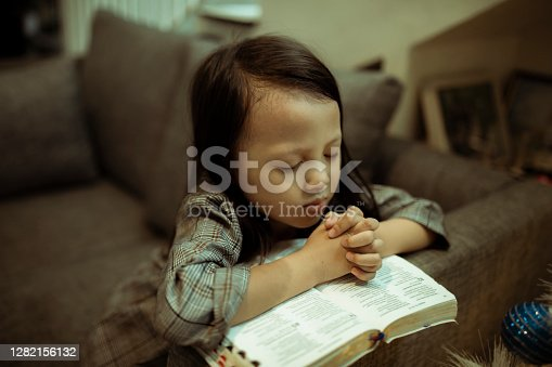 kid reading the holy bible and praying