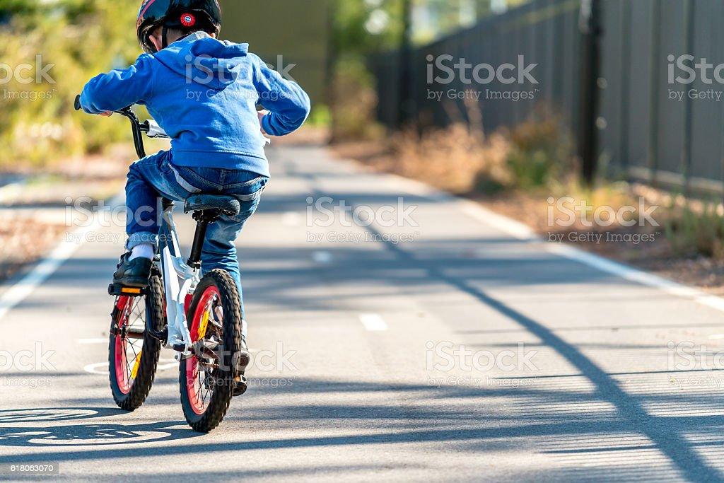 Kid riding his bicycle on bike lane stock photo