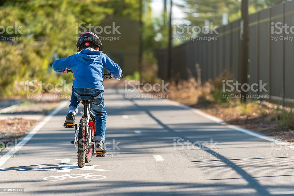 Kid riding his bicycle on bike lane stock photo