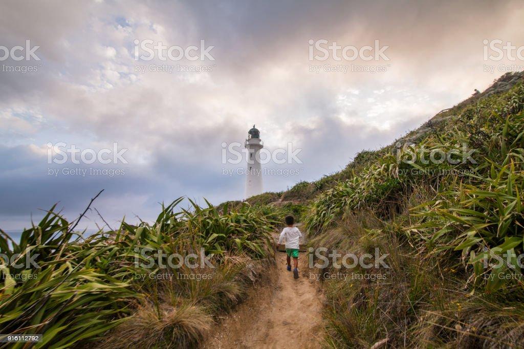 Kid running towards Castlepoint Lighthouse. stock photo