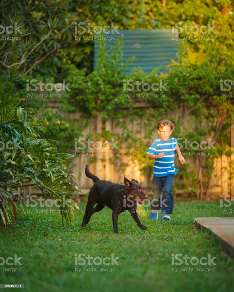 kid running with his dog royalty-free stock photo