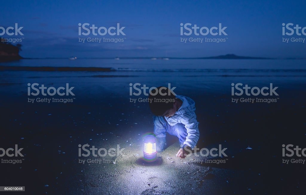 Kid searching sand with lantern. stock photo
