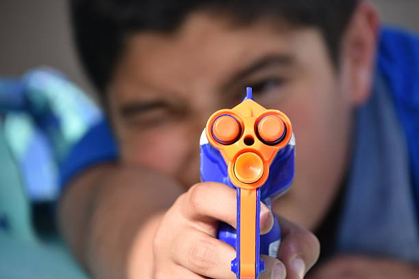 Kid shooting a toy gun stock photo