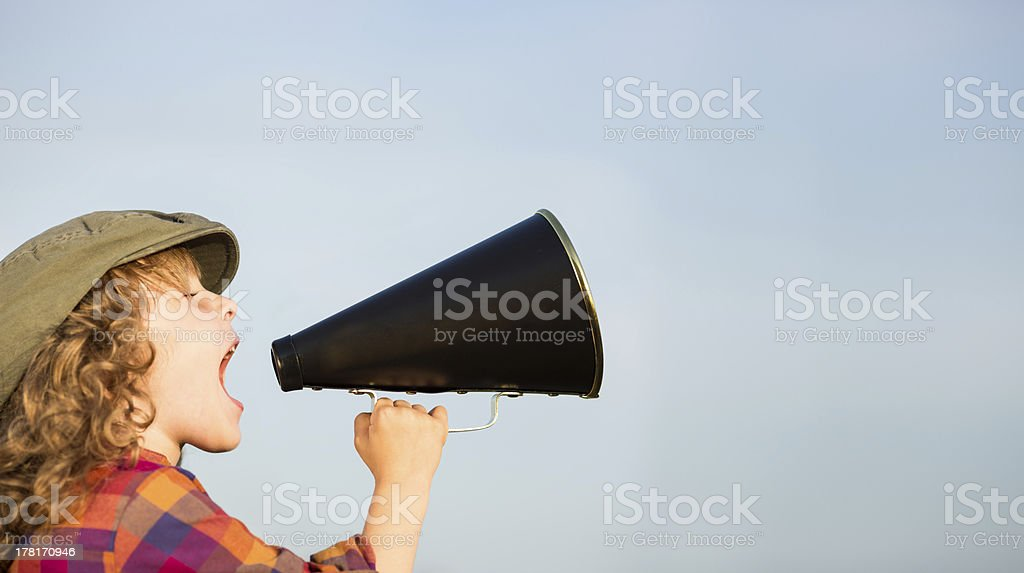 Kid shouting through megaphone stock photo