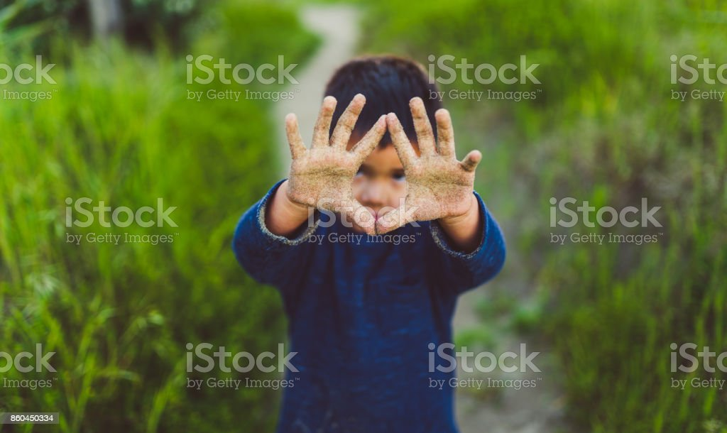 Kid showing hand dirty with sand. stock photo