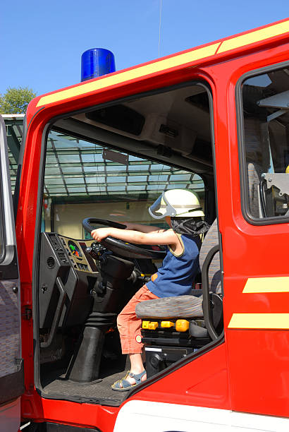 Kind sitzt am Lenkrad of fire engine – Foto