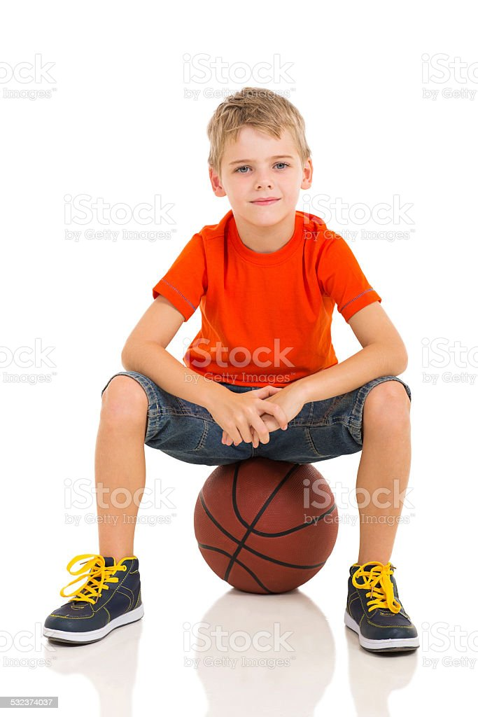 kid sitting on a basketball stock photo