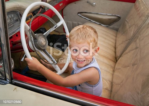 Beautiful child sitting on old American car 50s / 60s years, holds steering wheel and pretends to drive it.Caucasian white baby boy.