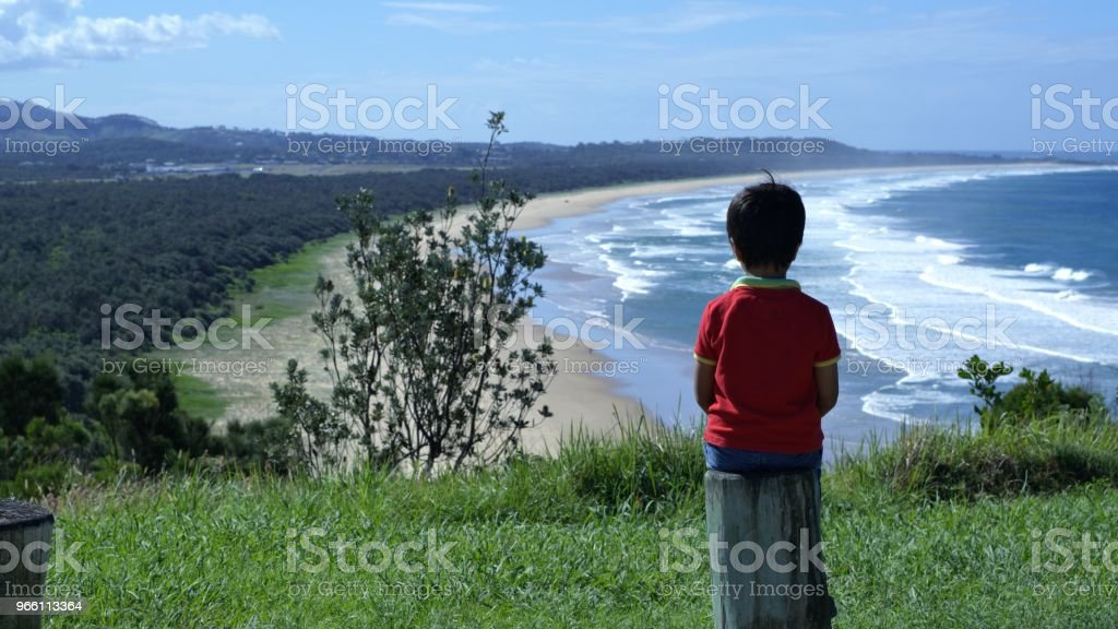 Jongen zit op houten paal kijken panoramisch uitzicht op zee, land - Royalty-free Alleen kinderen Stockfoto
